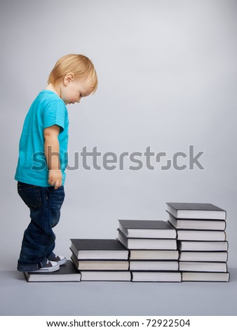 A kid begins his education represented as a steps made of books - stock photo