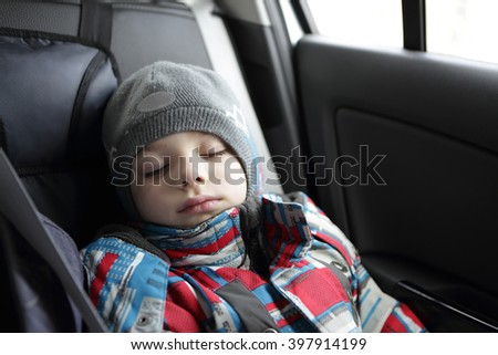 A kid boy sleeping in the car - stock photo