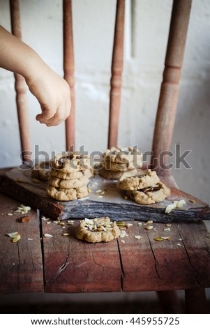 A kid helping to decorate chocolate filled cookies made of different healthy flours with seeds and nuts. Dark photo. Selective focus. Also available in horizontal format.