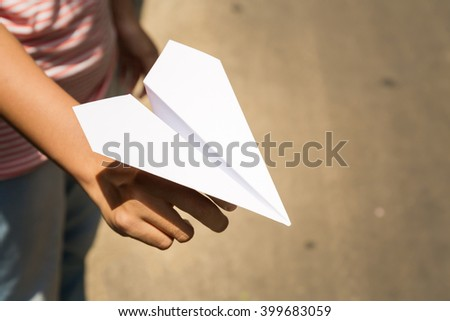A kid holding a paper plane - stock photo