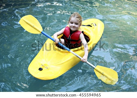 A kid kayaking in beautiful green water