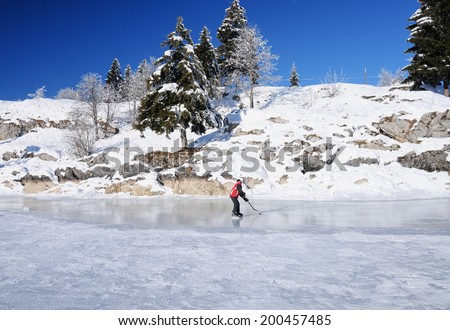 A kid playing ice hockey on a frozen lake, Canton Vaud, Switzerland - stock photo