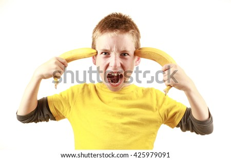 A kid pretending that bananas are guns - stock photo