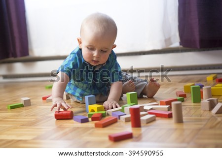 A kid toddler playing  wooden toys at home or nursery - stock photo