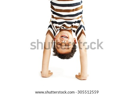 A kid upside down smiling to the camera.  Isolated on white background  - stock photo