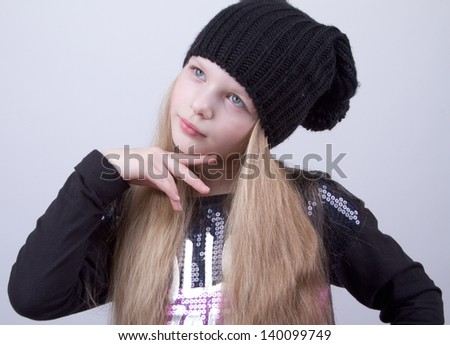 A kid wearing black hat posing