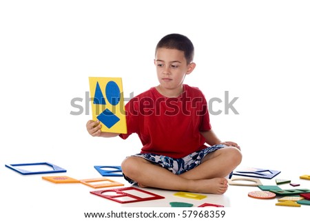 A kindergarten boy checking out the puzzle of shapes he's just assembled.  Isolated on white. - stock photo