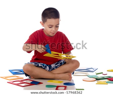 A kindergarten boy happy to have found the right puzzle piece from among many.  Isolated on white. - stock photo