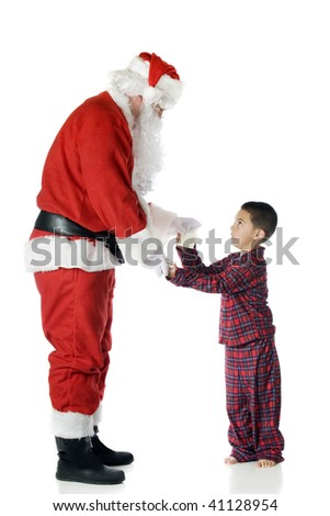 A kindergarten boy in plaid pajamas handing a glass of milk and some cookies to Santa.  Isolated on white. - stock photo