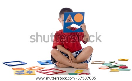 A kindergarten boy peeking through the frame of a puzzle he's assembling.  Isolated on white. - stock photo
