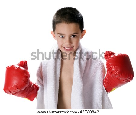 A kindergarten boy wearing boxing gloves and a towel around his neck, ready for a challenge.  Isolated on white. - stock photo