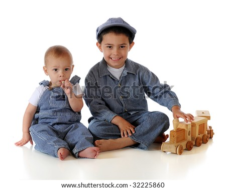 A kindergartner and his baby brother dressed as RR engineers while playing with a toy wooden train.  Isolated on white. - stock photo