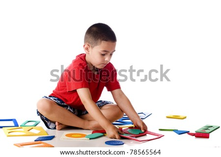 A kindergartner attempting to assemble a puzzle of colorful shapes.  Isolated on white. - stock photo