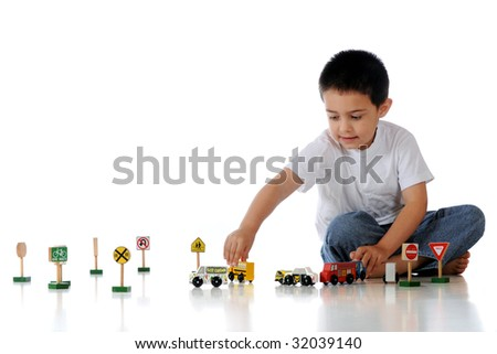 A kindergartner playing with an assortment of wooden cars, trucks and traffic signs.  Isolated on white. - stock photo