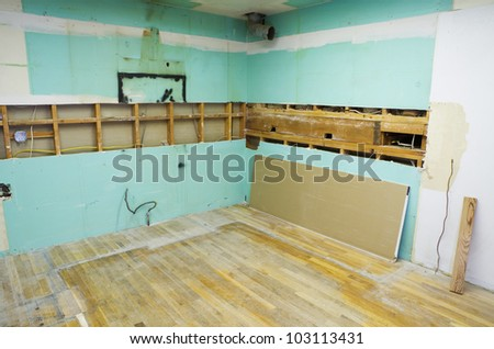 a kitchen near the start of a home remodel with all of the cabinets and appliances removed - stock photo