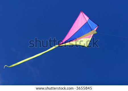 a kite flying against a blue sky in sunlight, bright colors and streaming tail - stock photo