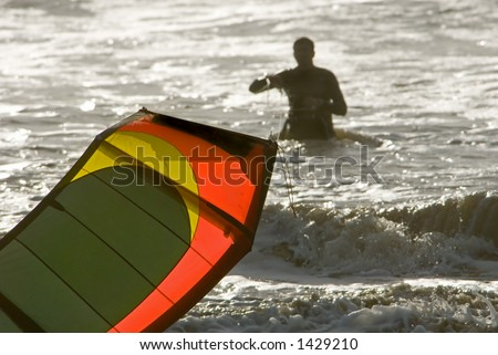 A kite surfer and his colorful kite are silhouetted against the ocean. - stock photo