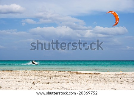 A kite surfer gliding at high speed around the beach Cinta, Sardinia - stock photo