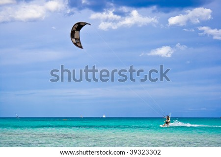 A kitesurfer gliding near the beach La Cinta, Sardinia - stock photo
