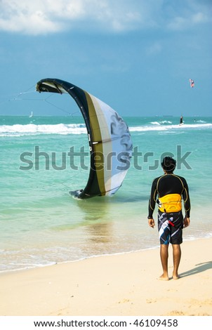A kitesurfer inspecting a colleagues kite thats about to take off - stock photo
