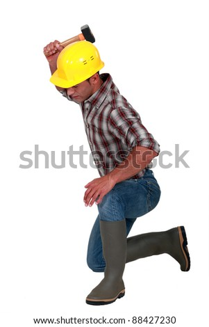A kneeled carpenter with a hammer. - stock photo