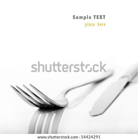 a Knife and fork stacked up on a pure white background - stock photo