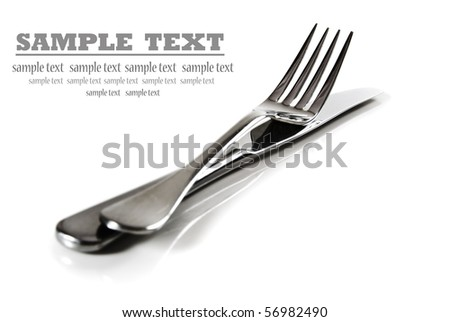 a Knife and fork stacked up on a pure white background with space for text -shallow depth of field - stock photo