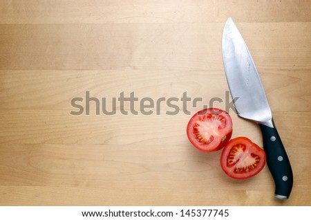 A knife and two halves of a tomato on a chopping board - stock photo