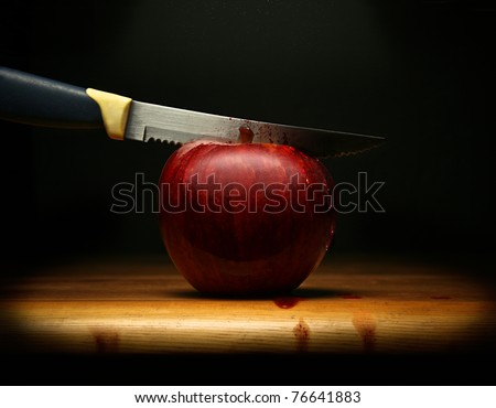 A knife cutting a red apple and blood flowing, on dark background. - stock photo