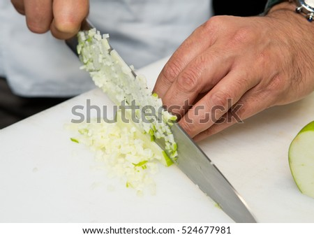 A knife cutting thin cubes of fresh organic green apple, on a white cutting board.