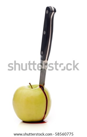 A knife in a bleeding green apple on white - stock photo