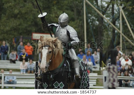 A knight on a horse preparing for a jousting tournament. - stock photo