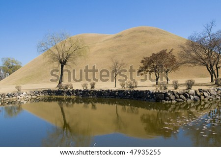 A Korean burial mound (Dolmen) from the ancient Silla kingdom, reflected in the calm waters of a pond in the foreground. - stock photo