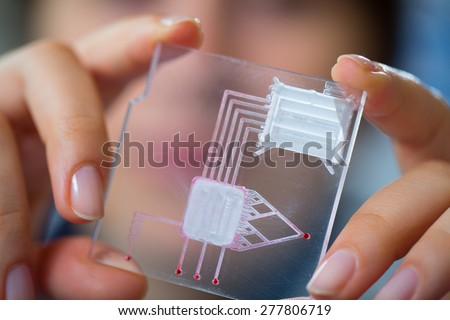 A lab on chip is device integrates several laboratory processes in one device, in woman hand - stock photo