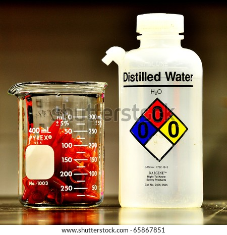 a laboratory distilled water bottle and a pile of eppendorf - stock photo