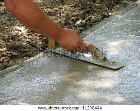 a laborer floats a new concrete sidewalk - stock photo