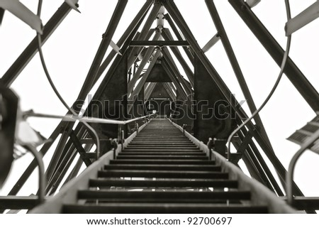 A ladder that leads to the top of a Radio/Communication Mast taken in Black & White. - stock photo