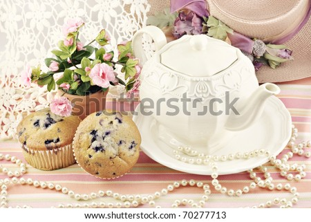 A ladies pretty tea party with blueberry muffins, antique lace and pearls - stock photo