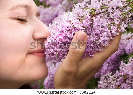 a lady enjoying the smell of some lilacs