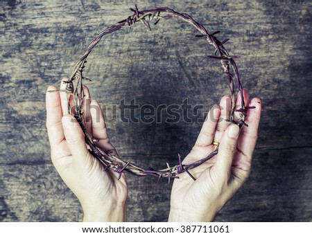 A lady hands holding old metal Barbed Wire made like the crown of thorns of Jesus  can be used for Christian concept , easter concept - stock photo