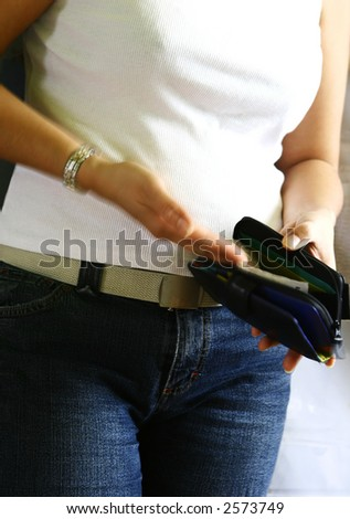 A lady in motion of putting  loose coins in a purse. - stock photo