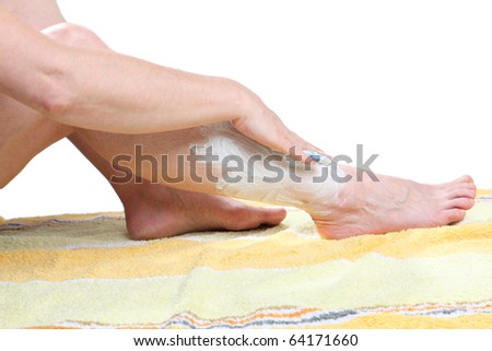 A lady is creaming her legs on a towel