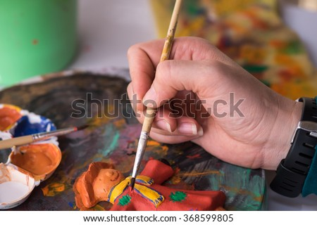 A lady painting on clay doll for art learning experience background with selective focused point - stock photo