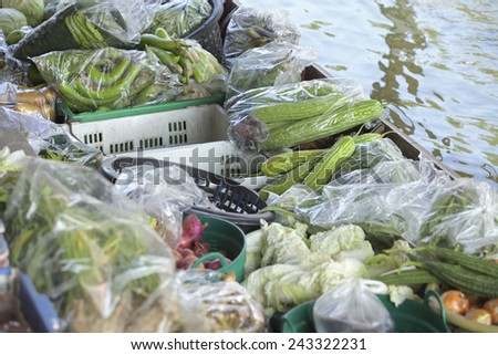 A lady selling fruit from her boat at a floating market in Thailand. Image taken at Damnoen Saduak floating market near Bangkok. Taken from above on a bridge. - stock photo