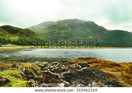 A lake and misty mountains in the Scottish Highlands - stock photo