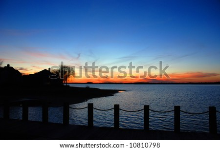 A lake house silhouette during the sunset with deep blue dramatic sky colors. Norman Lake, Northern Carolina, USA. - stock photo