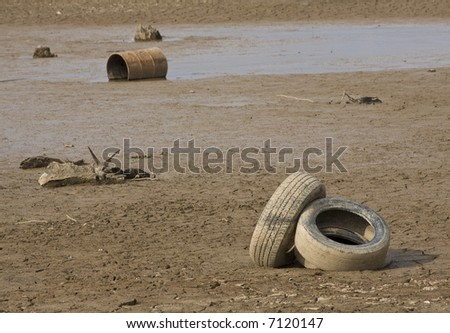 A lake in Atlanta dries up during a drought.  Focus on the tires. Litter and trash exposed after a lake dries.  Red clay lake bottom.