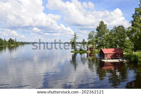 A lake in Sweden with reflection of the red house and trees in the water - stock photo