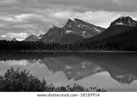 A lake in the Canadian Rockies shows its reflections of the mountains and sky; in black and white. - stock photo