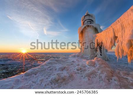 A Lake Michigan winter sunset illuminates the ices that encapsulates the St. Joseph northern pier. - stock photo